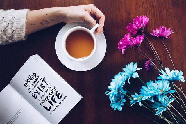 A cup of coffee and a vase of flowers on a table