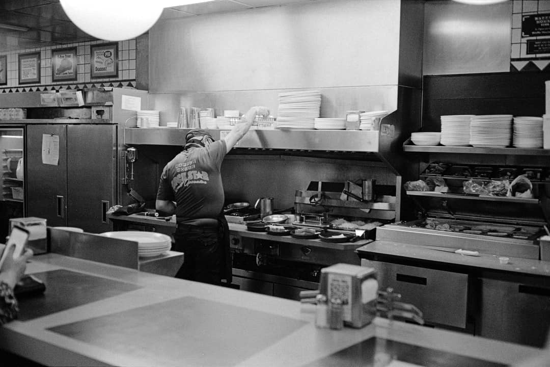 A person sitting on a kitchen counter preparing food